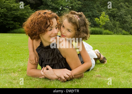 Kleines Mädchen hält ihre schöne Mutter im park - Stockfoto