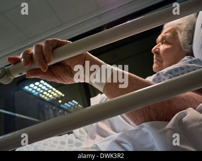 Nachdenklich traurig ältere Dame mit 100 Jahren im Krankenhaus Pflegebett in der Nacht - Stockfoto