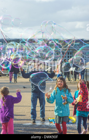 Straße Entertainer bläst Luftblasen für Kinder London South Bank.  Kinder spielen mit Luftblasen - Stockfoto