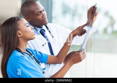Afrikanische Ärzte betrachten des Patienten Röntgen im Krankenhaus - Stockfoto