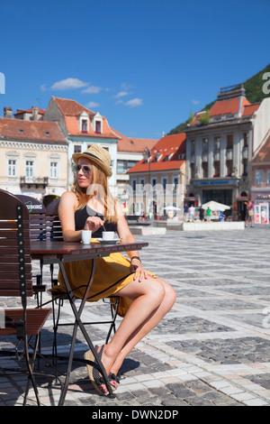 Frau sitzt im Café in Piata Sfatului, Brasov, Siebenbürgen, Rumänien, Europa - Stockfoto