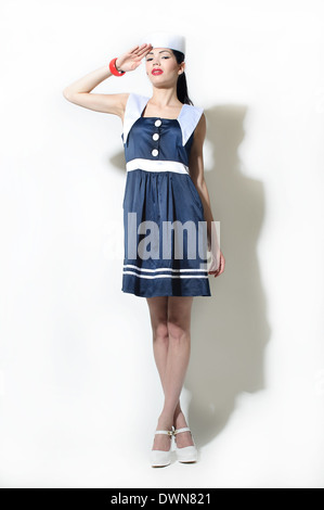 Ein weibliches Modell gekleidet in einen Seemann Kleid und Matrose Hut Grüßen in die Kamera schaut - Stockfoto