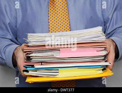 Überarbeitete Geschäftsmann mit einem Stapel von Papieren. Hautnah. - Stockfoto