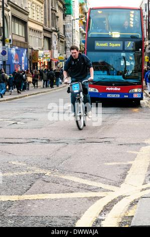 Radfahrer mit blauem Barclay Fahrrad ins New Oxford Street, vorbei an der Tottenham Court Road Kreuzung - Stockfoto