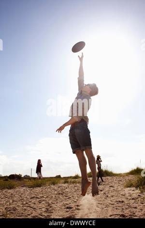 Junger Mann in der Luft fangen Kunststoffscheibe - Stockfoto