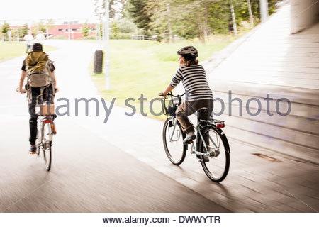 Bewegungsunschärfe von Vater und Tochter auf Fahrrädern auf Straße - Stockfoto