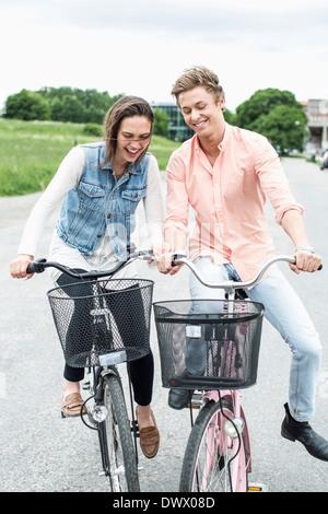 Junge Freunde genießen Fahrrad fahren auf Landstraße - Stockfoto