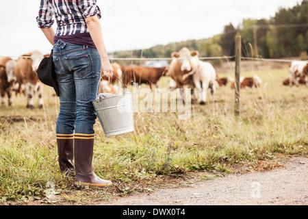 Geringen Teil der Bäuerin mit Eimer stehen am Feld mit Tiere grasen im Hintergrund - Stockfoto