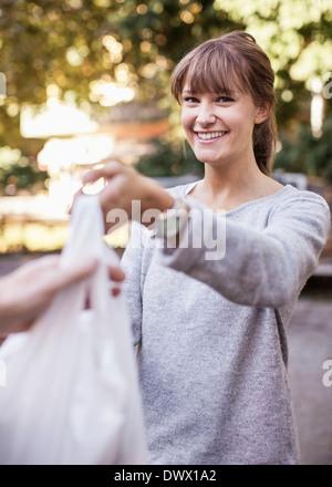 Porträt der jungen weiblichen Verkäufer Verkauf von Gemüse - Stockfoto