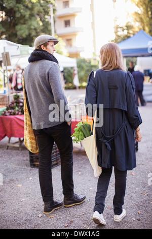 Rückansicht des jungen Paares mit Blattgemüse am Markt - Stockfoto