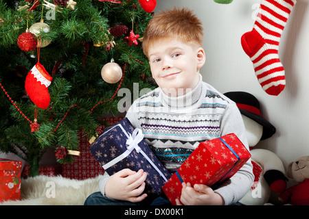 Glücklich lächelnden kleinen Jungen mit Weihnachts-Geschenk-Boxen in der Nähe von the Christmas tree - Stockfoto