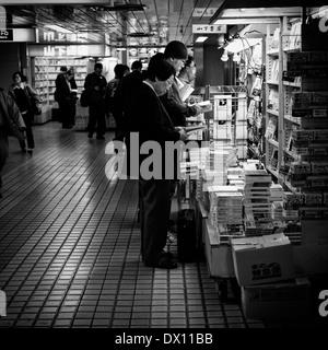 Männer lesen In unterirdischen Shinjuku, Tokyo, Japan - Stockfoto