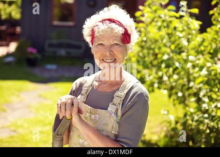 Portrait von glücklich senior Frau mit Gartengeräten im Garten stehen - Stockfoto