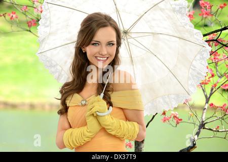 Porträt der jungen Frau im viktorianischen Kleid Holding-Dach im freien - Stockfoto
