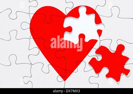 Ein rotes Herz Puzzle puzzle mit einem Stück auf der Seite, gutes Bild für ein gebrochenes Herz, Liebe, Romantik - Stockfoto