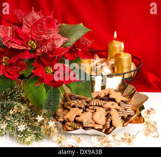 festlicher Advent Dekoration mit brennenden goldenen Kerzen, Weihnachtsstern Blume und Weihnachten Lebkuchen - Stockfoto