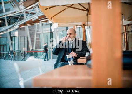 elegante modische Geschäftsmann auf dem Handy an der bar - Stockfoto