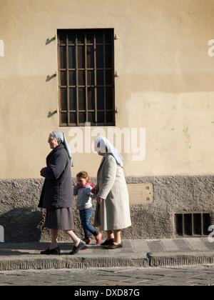 Gehen Sie an einem warmen März Morgen in Florenz zwei Nonnen für einen Spaziergang mit einem kleinen Kind - Stockfoto