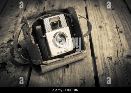 Eine alte Kamera im Etui original Vintage-Leder auf einem hölzernen Hintergrund gefiltert - Stockfoto