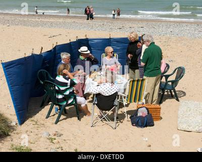 Gruppe von Menschen sitzen um einen Tisch mit einem Picknick am Strand in Cromer Norfolk England - Stockfoto