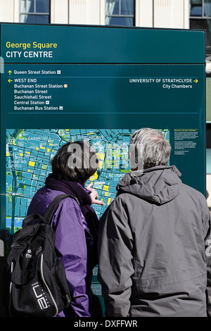 Zwei Touristen auf der Suche auf einer Karte von Glasgow City Centre, Glasgow, Schottland, UK - Stockfoto