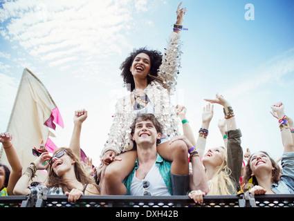 Jubelnde Frau auf ManÍs Schultern beim Musikfestival - Stockfoto