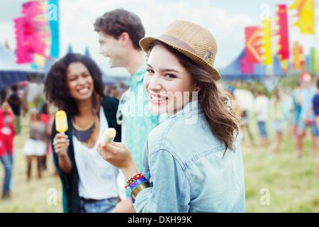 Porträt der Frau Essen aromatisierte Eis mit Freunden beim Musikfestival - Stockfoto