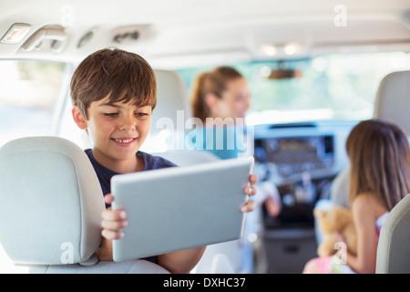 Fröhlicher Junge mit digital-Tablette im Rücksitz des Wagens