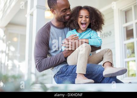 Vater kitzeln Tochter auf Veranda - Stockfoto