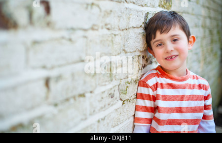Süsser Boy Grunge Wand gelehnt - Stockfoto