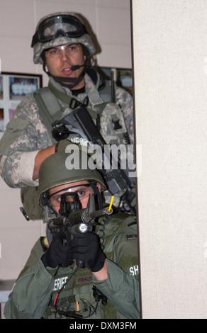 Sheriff SWAT-Teams auf der Suche nach einen Verdächtigen in einer Schule mass Casualty Incident Ausbildung. Waffe - Stockfoto