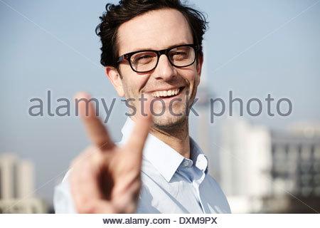 Porträt von lächelnden Mann zeigt Victory-Zeichen - Stockfoto