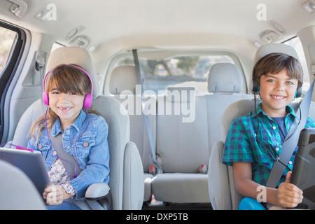 Porträt von glücklich Bruder und Schwester mit Kopfhörern mit digitalen Tabletten im Rücksitz des Wagens - Stockfoto