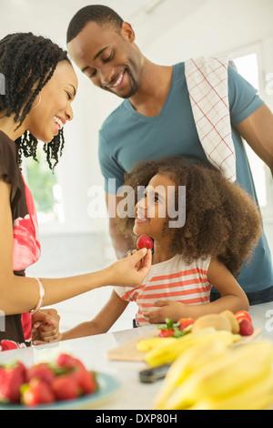 Glückliche Familie Essen Erdbeeren - Stockfoto