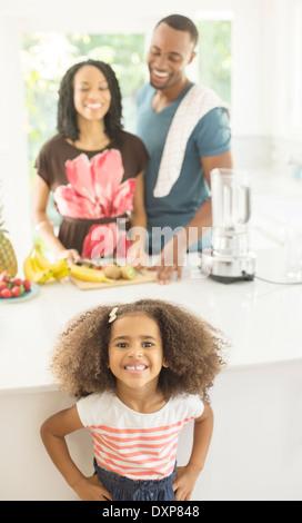 Porträt von begeisterten Mädchen in der Küche mit den Eltern im Hintergrund - Stockfoto