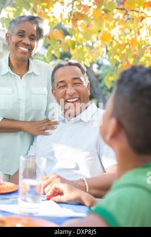 Großeltern und Enkel Lachen Terrassentisch - Stockfoto