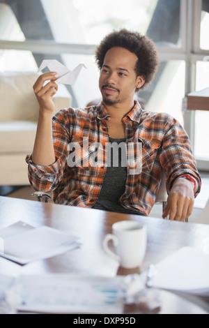 Nachdenklich kreative Unternehmer betrachten Origami Schwan im Büro - Stockfoto
