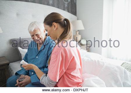 Häusliche Pflege Krankenschwester Medizin senior Mann im Schlafzimmer zu geben - Stockfoto