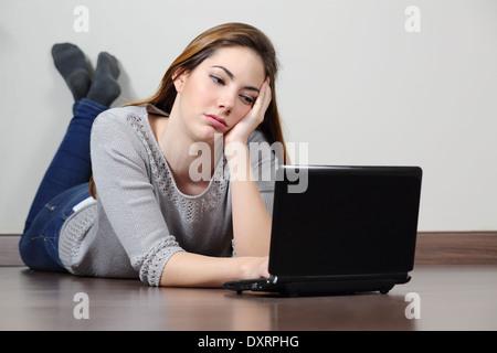 Gelangweilter Teenager Mädchen Surfen soziale Medien in einem Laptop, auf dem Boden zu Hause liegen. - Stockfoto