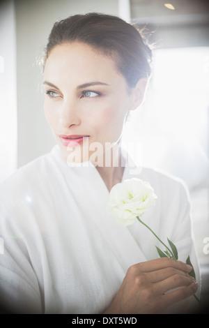 Frau im Bademantel halten weiße rose Nahaufnahme - Stockfoto