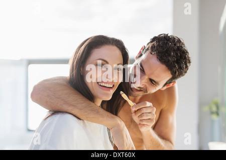 Mann versucht, WomanÍs Zähneputzen im Bad - Stockfoto