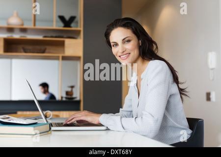 Porträt der lächelnde Frau mit Laptop am Tisch - Stockfoto