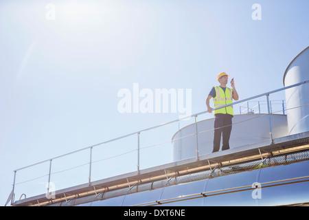 Arbeiter mit Walkie-talkie auf Plattform neben Silage Speichertürme - Stockfoto
