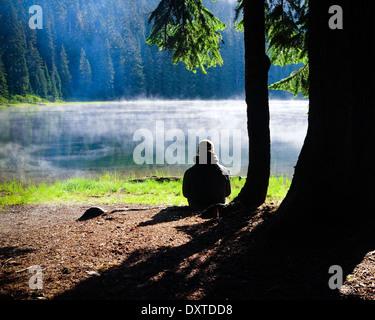 Mann sitzt an einem See am Morgen mit Nebel und Lagerfeuer Rauch über dem Wasser. - Stockfoto