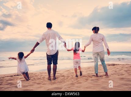 Glückliche junge Familie, die Spaß am Strand bei Sonnenuntergang Stockfoto