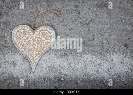 A Herz auf einem grauen Kalkstein-Hintergrund aus Holz geschnitzt - Stockfoto