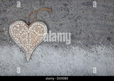 Herz auf grauem Kalkstein Hintergrund aus Holz geschnitzt - Stockfoto