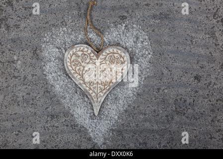 Herz auf Greystone Hintergrund mit Kunstschnee aus Holz geschnitzt - Stockfoto