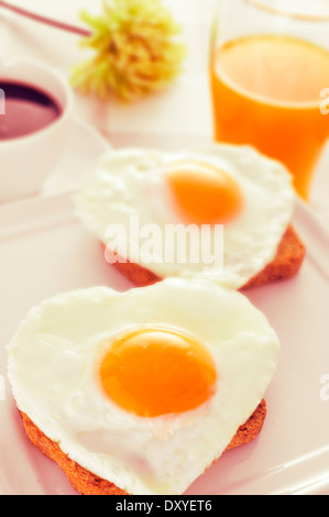 einige herzförmigen Spiegeleier auf Brot, eine Tasse Kaffee und ein Glas Orangensaft mit einem Retro-Effekt serviert - Stockfoto
