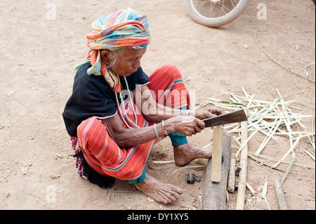 Karen Seniorin sitzt auf dem Boden mit einer Machete ein Stück Holz zu hacken.  Huay Pakoot Dorf, Nord-Thailand. - Stockfoto